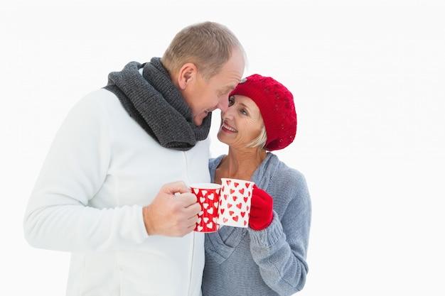 マグカップを持って冬の服の中で幸せな成熟したカップル