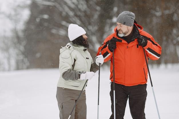 ウィンターパークで幸せな成熟したカップル。のんびりと森をトレッキングするアクティブウェア