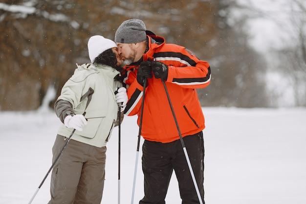겨울 공원에서 행복 한 성숙한 부부입니다. 여가 시간에 숲에서 트레킹하는 사람들 액티브웨어