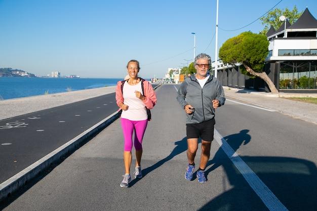 川岸に沿ってジョギング幸せな成熟したカップル。スポーツ服を着て、外を走っている白髪の男女。活動と年齢の概念