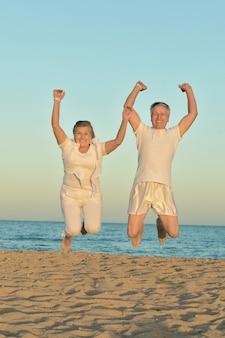 하늘을 배경으로 해변에서 점프하는 행복한 성숙한 커플