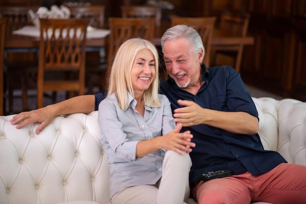 Счастливая зрелая пара смеется во время просмотра телевизора