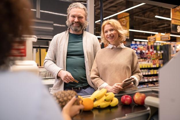 과일을 구입하고 신용 카드로 지불하려고하는 동안 슈퍼마켓에서 금전 등록기로 판매 사무원을보고 행복 성숙한 부부