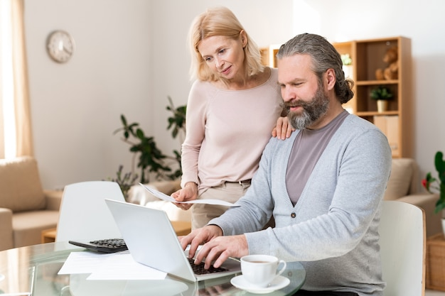 Happy mature couple looking at laptop display while one of them entering data after making calculations