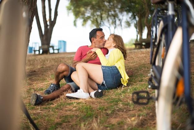 草の上に横たわってキスして幸せな成熟したカップル