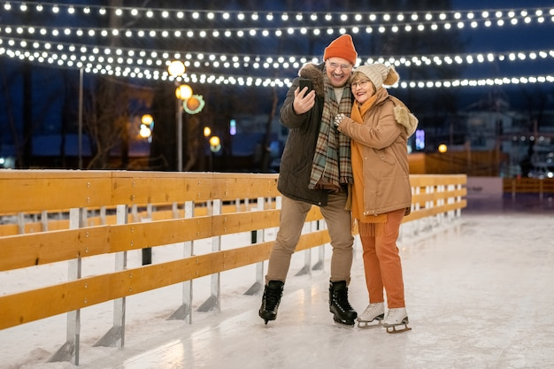 Happy mature couple making photo on mobile phone during his ride on ice rink in the park