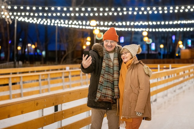 Happy mature couple making selfie portrait on mobile phone while standing on ice rink outdoors