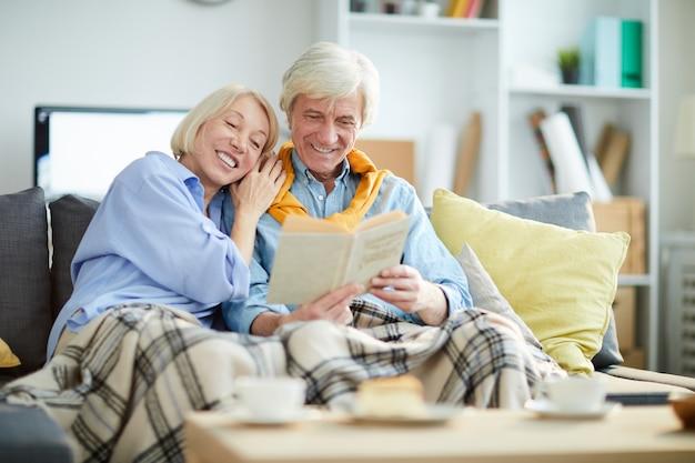 Happy mature couple reading book