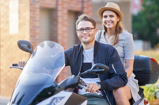 Счастливая зрелая пара, едущая на скутере в городе в солнечный день