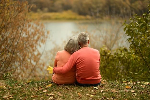 호수 근처에 앉아 있는 행복한 성숙한 커플, 뒷모습