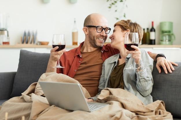 Счастливая зрелая пара, сидя на диване с бокалами красного вина, используя портативный компьютер и смеясь