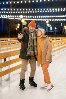 Happy mature couple on skates making selfie portrait on mobile phone while skating outdoors