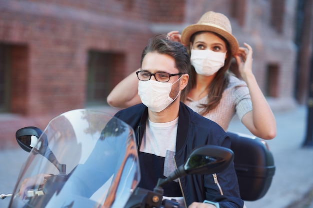 Счастливая зрелая пара в масках во время езды на скутере в городе в солнечный день