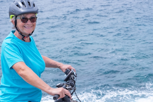Счастливая зрелая женщина велосипедиста, наслаждающаяся деятельностью на море с ее электрическим велосипедом. стоя на скале