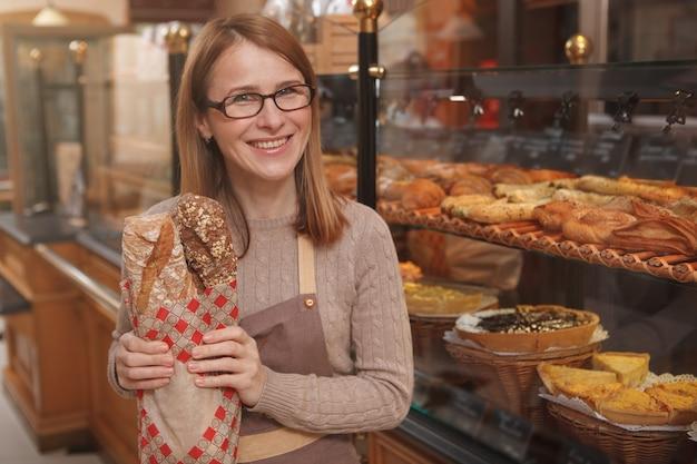 신선한 빵 한 덩어리를 들고 앞에 웃고 행복 성숙한 여성 베이커