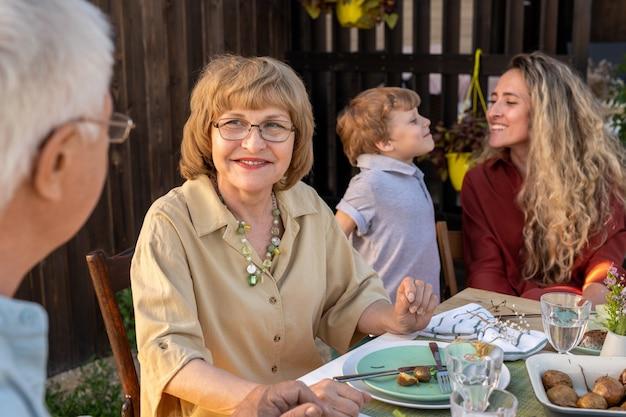 Счастливая зрелая женщина разговаривает со своим мужем во время ужина на открытом воздухе