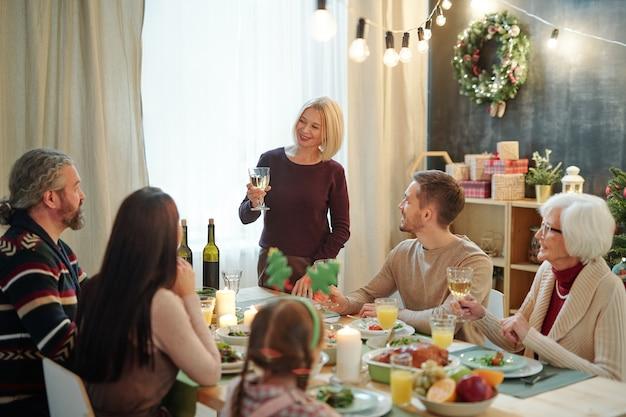 Счастливая зрелая женщина с бокалом вина делает праздничный тост за сервированным столом, глядя на свою семью во время ужина