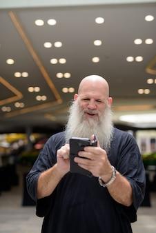 Счастливый зрелый красивый лысый бородатый мужчина с помощью телефона в городе на открытом воздухе