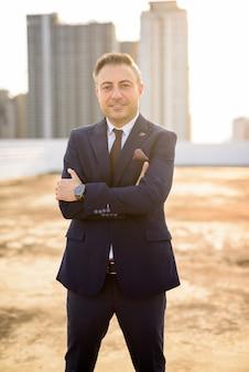 Счастливый зрелый красивый бизнесмен в костюме против вида на город