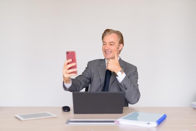 Счастливый зрелый красивый бизнесмен в костюме, делающий селфи на работе