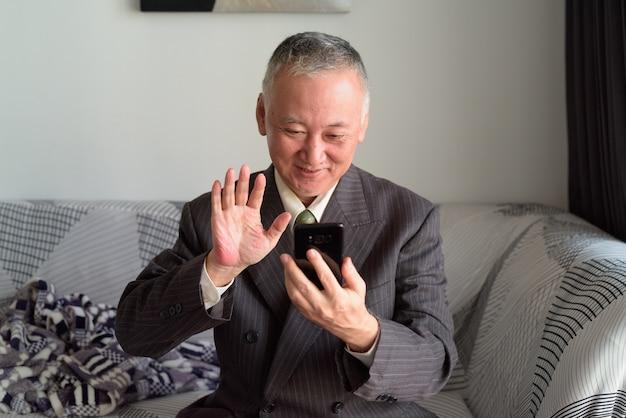 Счастливый зрелый японский бизнесмен звонит, оставаясь дома под карантином