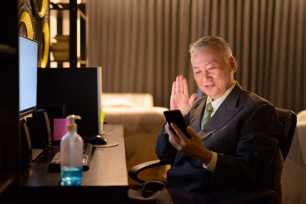Happy mature japanese businessman video calling with phone while working overtime at home late at night