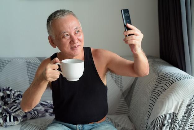 Счастливый зрелый японец пьет кофе и принимает селфи в гостиной дома