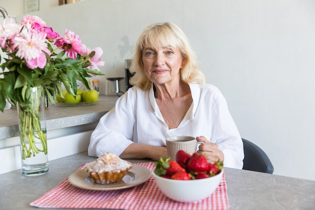 Happy mature lady sitting with cup of coffee