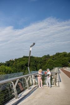 Счастливая зрелая дама с свернутым циновкой разговаривает с мужчиной на современном пешеходном мосту