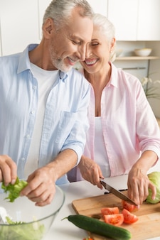 Happy mature loving couple family cooking salad