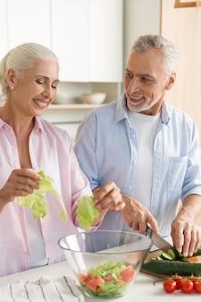 幸せな成熟した愛情のあるカップル家族サラダを調理