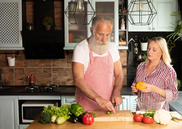 Счастливая зрелая любящая пара семьи стоя на кухне и готовя салат.