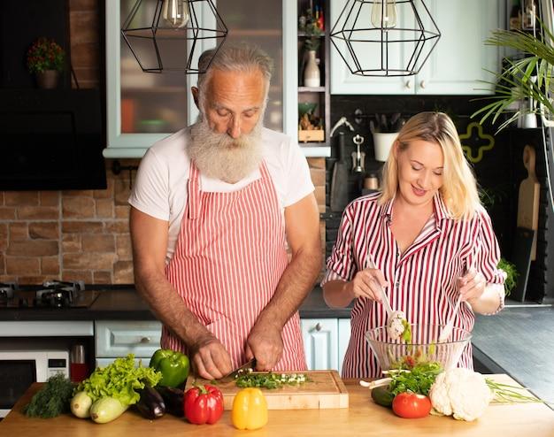 幸せな成熟した愛情のあるカップルの家族がキッチンに立ってサラダを調理します。