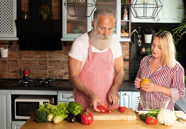 Happy mature loving couple family standing at the kitchen and cooking salad.