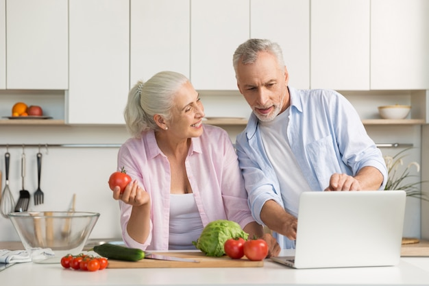 Happy mature loving couple family using laptop and cooking