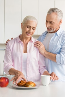 Happy mature loving couple at the kitchen near pastries