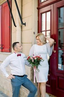 幸せな成熟した愛情のあるカップル、街の屋外、美しいヴィンテージの赤いドアの近くに立っています。