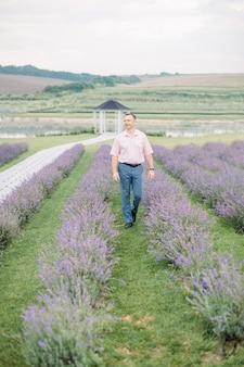 夏の日の彼の美しいラベンダー農園で満足のいく表情で歩いて、エレガントな服を着て幸せな成熟した男性農家