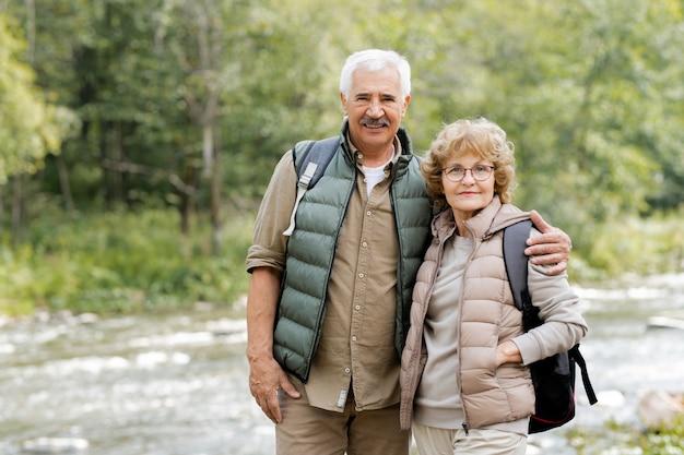 Счастливый зрелый турист мужского пола обнимает свою жену, пока оба стоят перед камерой на фоне лесной реки