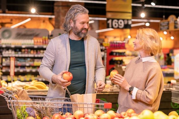 Счастливый зрелый мужчина и его жена выбирают свежие яблоки, стоя у дисплея с фруктами в супермаркете во время покупок