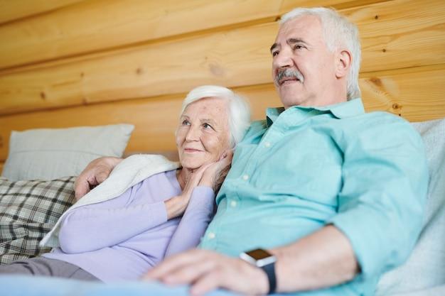 집에서 나무 벽으로 소파에서 휴식을 취하는 동안 행복 한 성숙한 남자와 그의 아내가 함께 텔레비전을보고