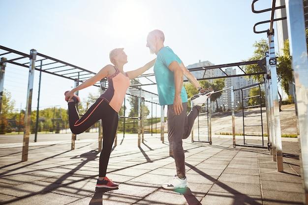 Счастливые зрелые мужчина и женщина в спортивной одежде вместе разогреваются на стадионе утром, когда они