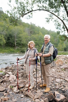 幸せな成熟した男と川沿いの石の上に立っている間あなたを見てトレッキングスティックを持つ女性