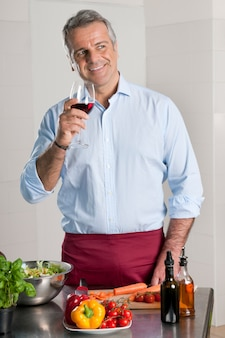Happy mature man drinking a glass of red wine while preparing the food for the dinner at home