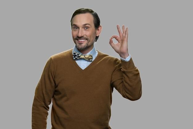 손가락으로 확인 몸짓 행복 성숙한 남자입니다. 회색 배경에 서있는 쾌활 한 백인 남자.