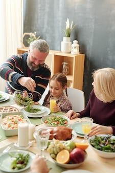 冬休みの家族の夕食の間にお祝いのテーブルで彼の愛らしい孫娘にサラダを与える幸せな成熟した男