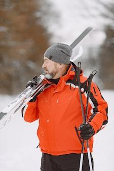 ウィンターパークで幸せな成熟した男。のんびりと森をトレッキングするシニアアクティブウェア