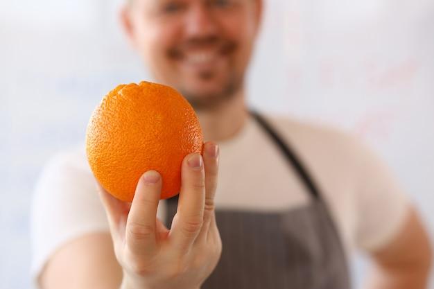 幸せな成熟した男はオレンジ色の果物を保持しています。