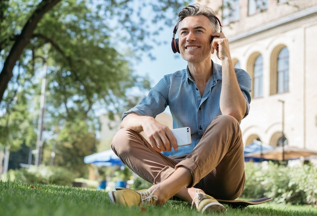 Happy mature man listening to music on headphones, relaxing in park