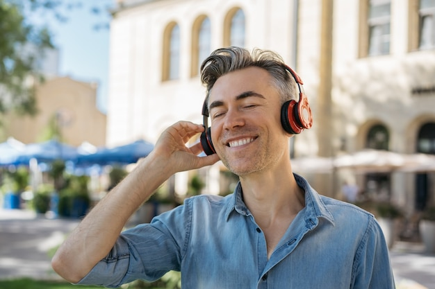 Happy mature man listening to music on headphones